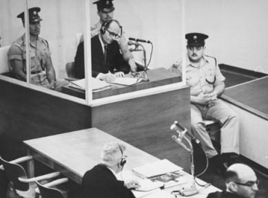 Eichmann em seu julgamento em Israel em  maio de 1961, com seu advogado Robert Servatius (centro) e o promotor Gideon Hausner (canto direito). Fonte:  United States Holocaust Memorial Museum.